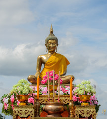 Buddha statue with incense sticks and candles