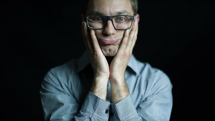 Bored portrait of caucasian man in glasses black background
