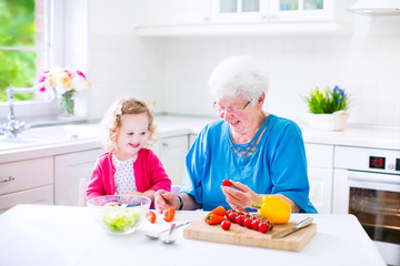 Adorable grandmother and little girl making salad