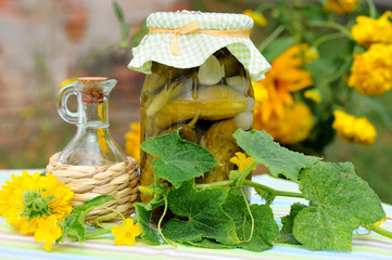Glass jar of homemade preserves (cucumbers) with leaves