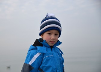 Portrait eines Kindes in Winterkleidung am Meer