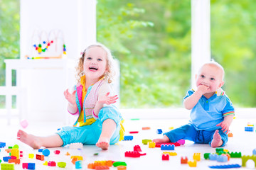 Little brother and sister playing with colorful blocks