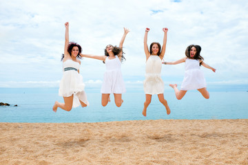 Four girlfriends jumping on beach