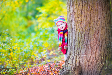 Little cute girl having fun in an autumn park