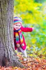 Little funny girl having fun in an autumn park