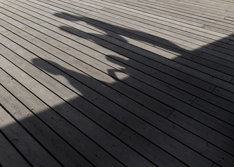 Shadows of a family walking on a wooden plank