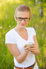 portrait of young fair-haired woman looking at mobile phone