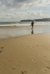 Hombre con paraguas paseando por la orilla de la playa