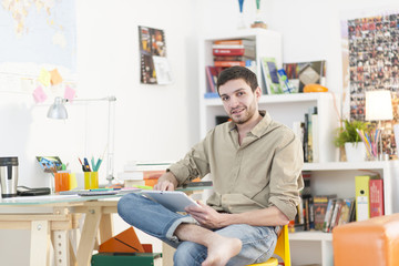 young student sits at his desk and surf on a digital tablet