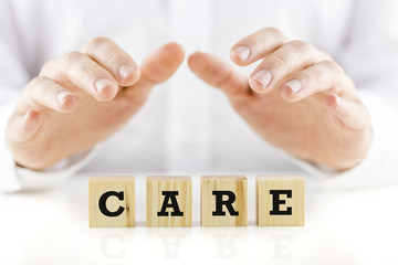 Care on wooden cubes with protective hands