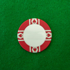 Red and white Casino chip on green table