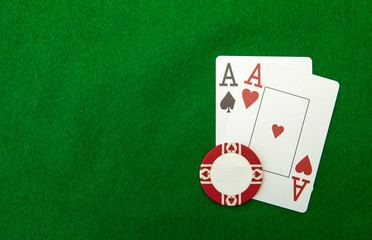 Cards showing pair of aces with chip on green background