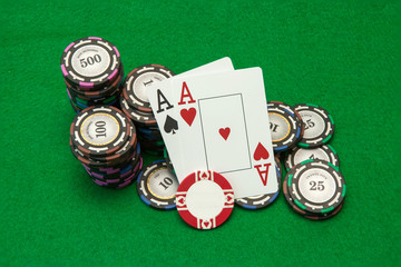 Cards showing pair of aces with chips on green background