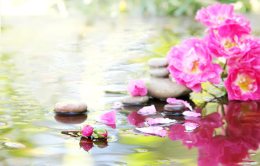 Spa stones with drops and rose in water