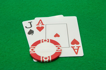 Jack and ace blackjack hand cards with chip on green background