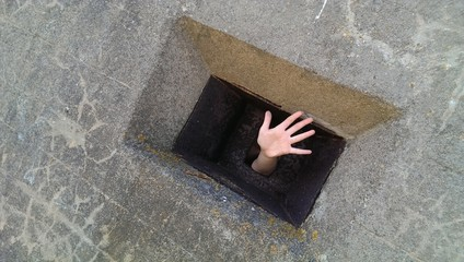 The hand popped out of small black window of old cincrete fort