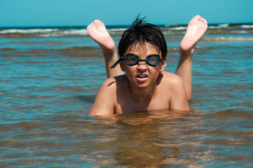 boy swims in the sea with glasses for swimming