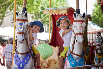 Cute kids, riding on a carousel