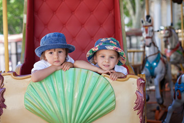 Cute kids, riding on a carousel