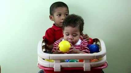 Brothers playing with multicolored balls