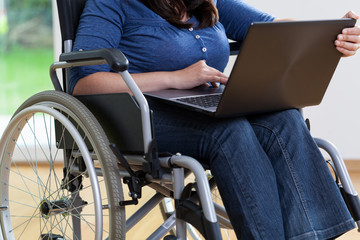 Handicapped woman on wheelchair using laptop