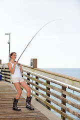Woman fishing from a pier