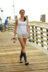 Woman walking on a fishing pier with fishing pole