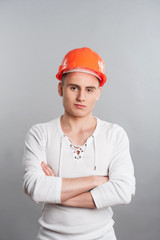 Portrait of a young confident worker in helmet isolated on grey