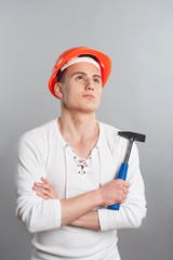 Portrait of a young confident worker in helmet holding hammer