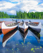 Canoes reflected on a turquoise lake, Quebec, Canada