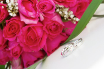 wedding rings and bridal bouquet over white