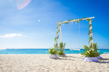 wedding swing decorated with flowers on tropical sand beach, out