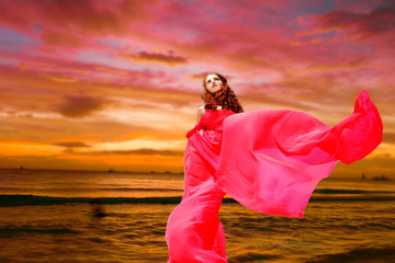 young beautiful woman in red dress on tropical sea sunset backgr