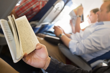 Reading books in airplane.