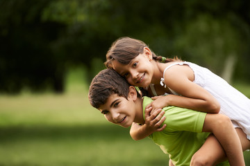 children boy and girl in love running piggyback park