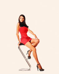 Studio shot of young woman sitting on bar stool
