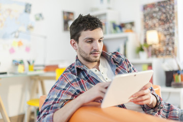 young student lying on a couch surfing  the web  on his digital