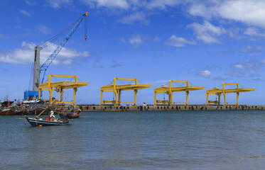 Fishing boat parking at industry cranes and cargo on port