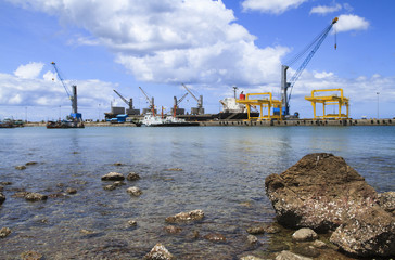 Ship yard with heavy crane at rock beach