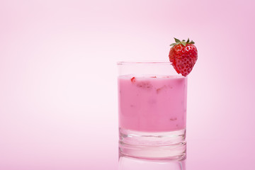 Fresh strawberry smoothie in a glass against pink background