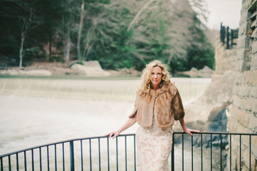 Beautiful Woman Wearing Vintage Fur in front of Waterfall