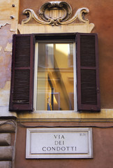 window with shutters on the street Via del Condotti, Rome, Italy