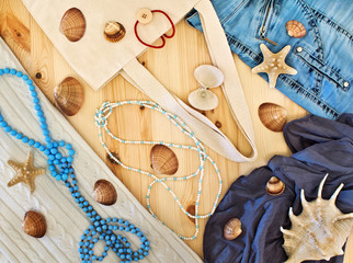 Women's clothing, beads and seashells on a wooden background.
