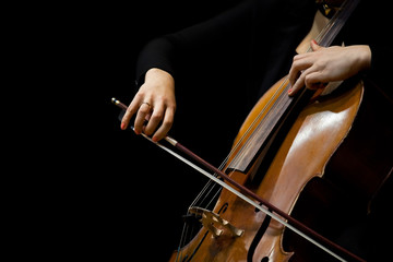 Hands girl playing cello on a black background