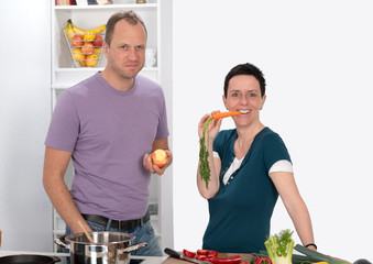 man and woman eating carrot and apple