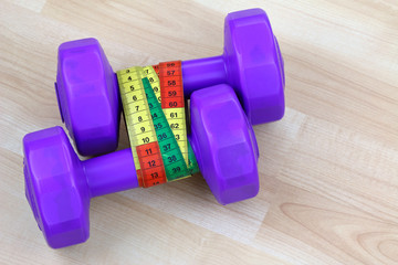 Purple dumbbells with measuring tape