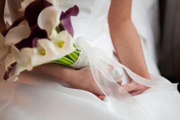 Le mani della sposa delicatamente appoggiate sul vestito