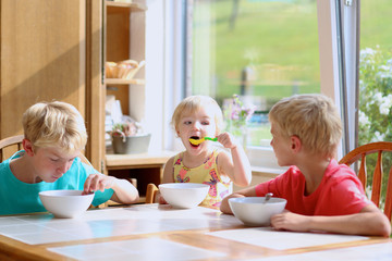 Group of happy kids having healthy breakfast in the kitchen