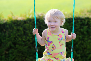 Happy little girl enjoying swing in sunny backyard garden