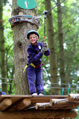 Happy boy enjoying a climbing adventure in activity park